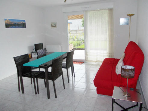 le séjour avec table, chaises et canapé, et la terrasse orientée S-O